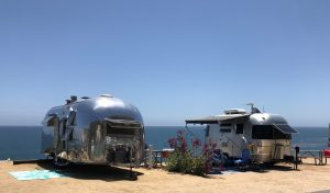 Two Air Stream RV Campers With a Great Ocean View Camping right on the Sandy Shore.